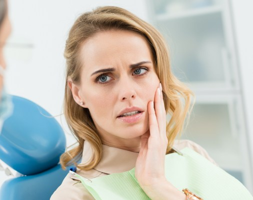 A woman with jaw pain listening to a dentist.