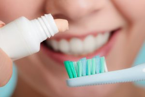 woman squeezing whitening toothpaste onto toothbrush