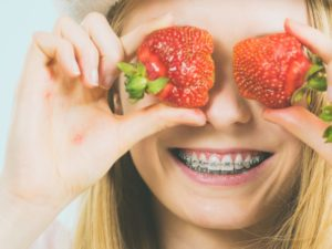 Smiling teen with braces in Mt. Holly holding strawberries