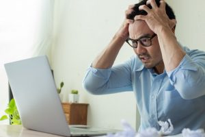 stressed person trying to find out if they have a dental emergency by searching on their computer