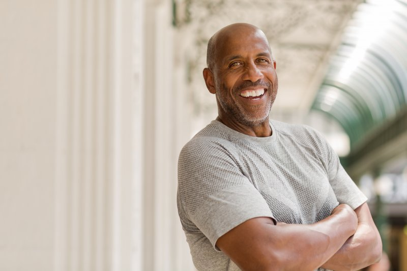 Mature man with dental implants smiling in gray shirt