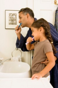 father and daughter brushing teeth to maintain oral health