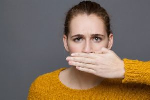 Woman with oral bacteria covering her mouth