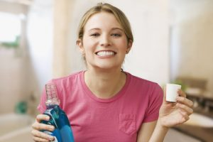 woman rinsing with mouthwash to maintain a healthy mouth
